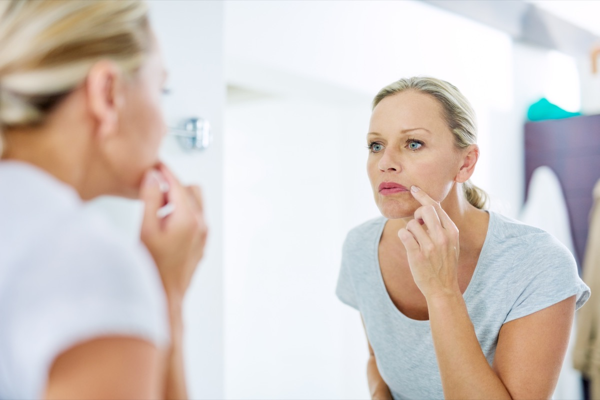 Mature woman inspecting her skin in front of the bathroom mirror.