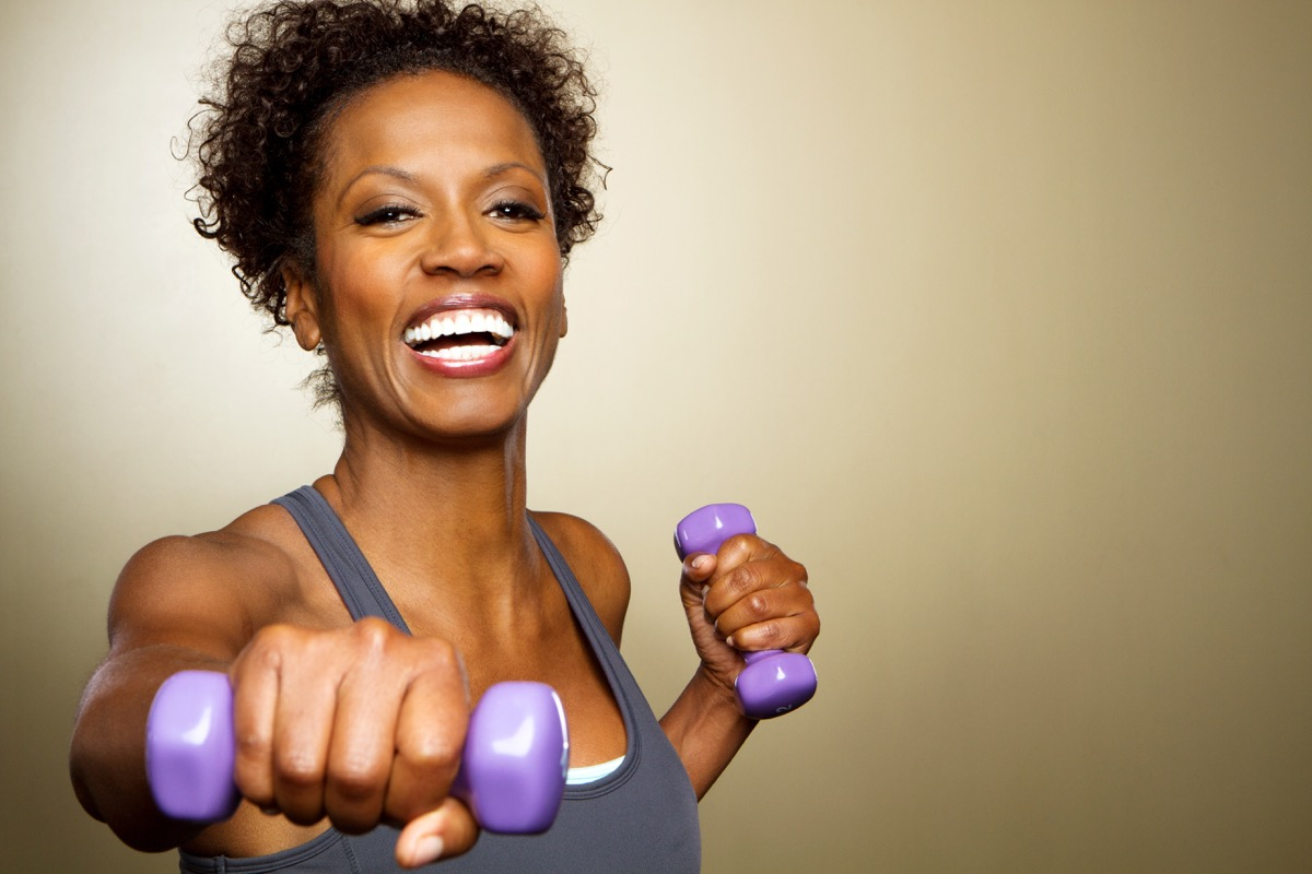 Happy fitness woman lifting dumbbells smiling and energetic